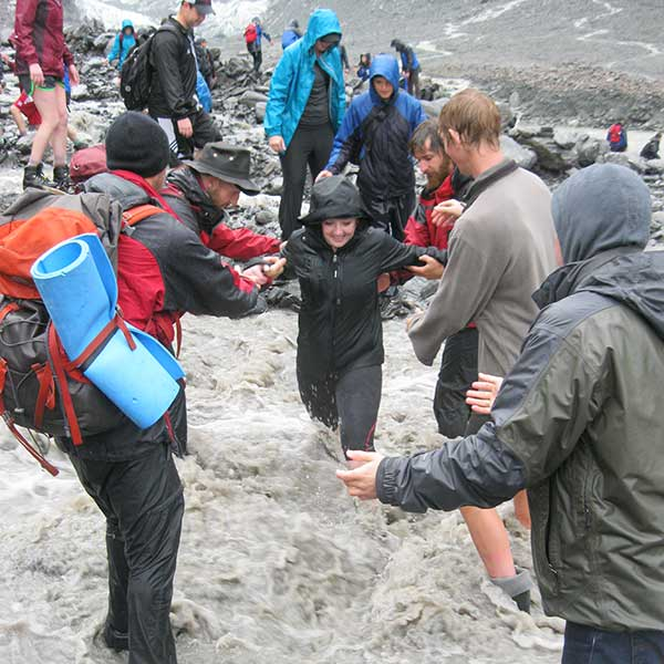Photo of team and guides trekking through glacial river in New Zealand